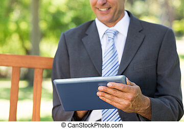 Midsection of businessman using digital tablet
