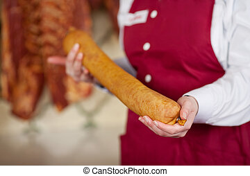 Midsection Of Butcher Holding Sausage