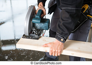 Midsection Of Carpenter Using Electric Saw To Cut Wood