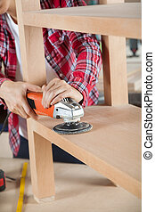 Midsection Of Carpenter Using Sander On Shelf