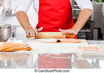 Midsection of male chef rolling ravioli pasta sheet at counter in commercial kitchen