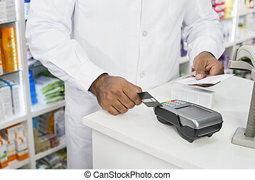 Midsection Of Chemist Holding Receipt While Swiping Credit Card