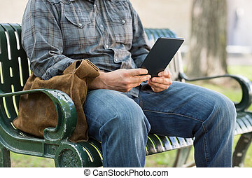 Midsection Of College Student Using Digital Tablet