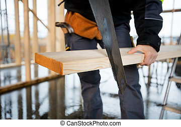 Midsection Of Female Carpenter Using Saw To Cut Plank