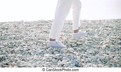Midsection of legs of senior woman walking on rocky beach by lake.