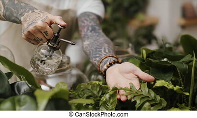 Midsection of man florist standing in flower and plant shop, spraying plants with water.