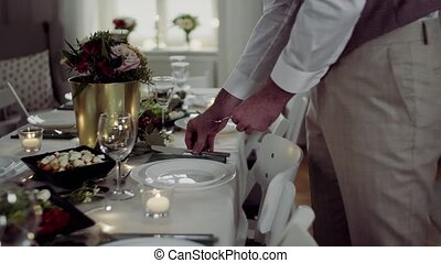Midsection of men dressed in suits setting a table for an indoor party.