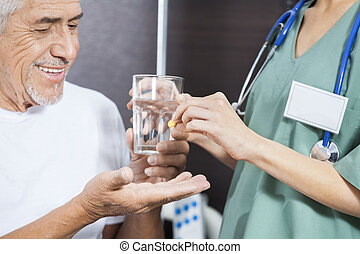 Midsection Of Nurse Giving Medicine And Water To Patient - ...