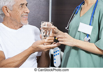 Midsection Of Nurse Giving Medicine And Water To Senior Patient