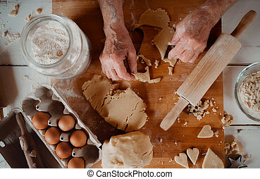 Midsection of old woman making cakes in a kitchen at home. Top view.