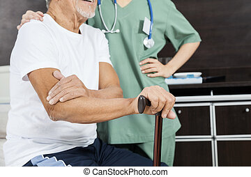 Midsection Of Patient With Nurse In Rehab Center