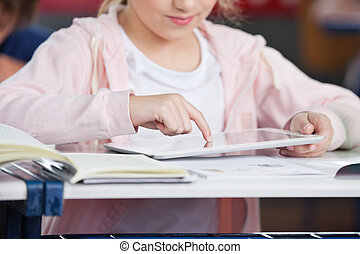 Midsection Of Schoolgirl Using Tablet At Desk