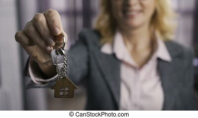 Midsection of senior estate agent presenting keys
