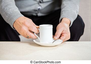 Midsection Of Senior Man Holding Coffee Cup