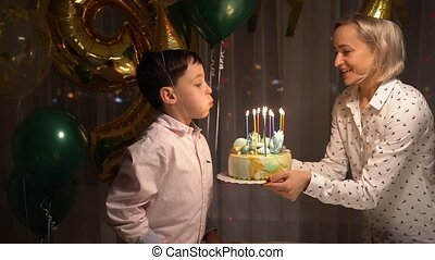 Midsection of sweet cheerful toddler boy, blowing candles on cake and clapping hands during his birthday party at home.