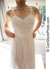 Midsection of woman in wedding dress standing at home