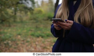 Midsection of woman surfing the net on smart phone -...