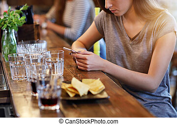 Midsection of woman texting in restaurant