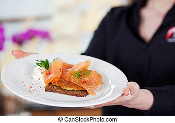 waitress serving salmon on bread - midsection view of a ...