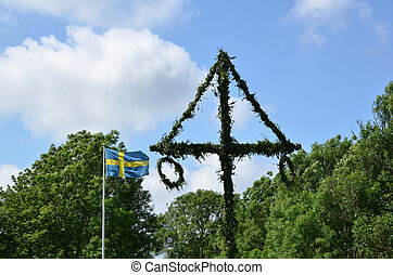 Swedish midsummer pole and swedish flag at green trees and blue sky.