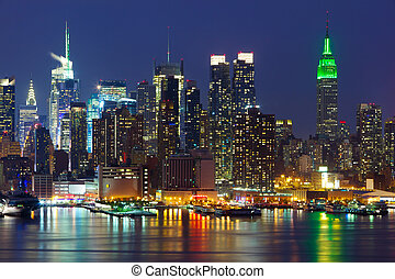 New York City midtown skyline at night over Hudson river