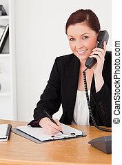 mientras, mujer, oficina, pelirrojo, sentado, bloc, joven, escritura, mirar, llamar, bueno, traje