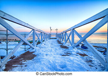 MIETKOW, POLAND - FEBRUARY 01, 2021: Pier on the frozen Mietkow Lake, just after sunset, during extremely low temperatures. Poland, Europe.