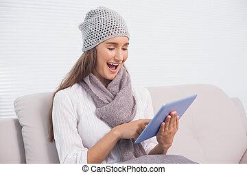 mignon, brunette, hiver, elle, séance, chapeau, tablette, gai, sofa, défilement, confortable