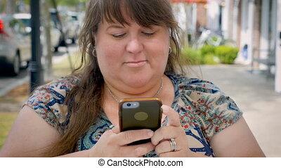 mignon, femme, grand, app, texting, curvy, téléphone, sourire, trottoir, intelligent