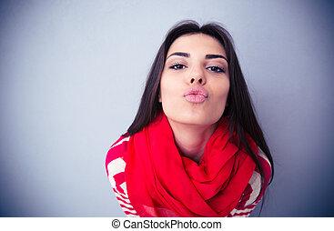 mignon, femme, gris, sur, appareil photo, fond, baisers
