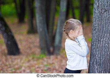 mignon, girl, jouant peau cycle recherche, près, arbre, dans, automne, parc