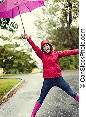 mignon, jeune femme, sauter, à, parapluie