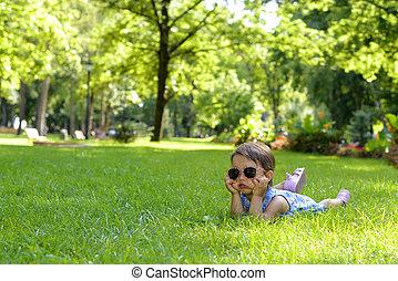 mignon, peu, enfantqui commence à marcher, girl, pose, dans, les, herbe, sur, a, ensoleillé, jour été