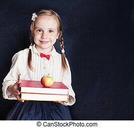 mignon, peu, school., heureux, tableau noir, books., dos, space., arrière-plan rouge, enfant, écolière, copie, vide, pomme