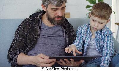 mignon, peu, sien, famille, séance, home., concept., moderne, père, conversation, quoique, toucher, utilisation, enfant, aimer, table, sofa, technologie, écran, heureux