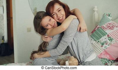 mignon, portrait, elle, séance, embrasser, quoique, lit, regarder, clair, appareil photo, ensemble, mère, chambre à coucher, maison, fille souriante, heureux