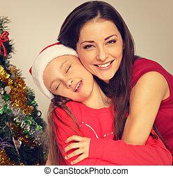 mignon, yeux, fourrure, fille, santa, elle, clause, arbre vert, naturel, arrière-plan., embrasser, fermé, mère, studio, sourire, apprécier, chapeau, noël, heureux