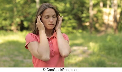Migraine girl in the park - Girl with a headache in a summer...