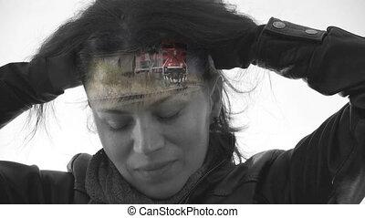A conceptual facial shot of a woman experiencing pain from a migraine headache.