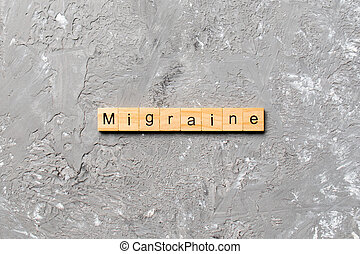 Migraine word written on wood block. Migraine text on cement table for your desing, concept