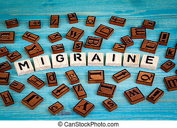 migraine word written on wood block. Wooden alphabet on a blue background
