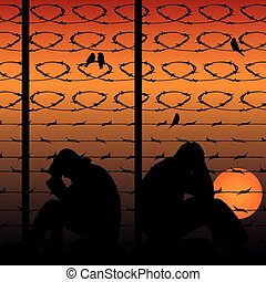 Migrant refugees behind barbed wire, silhouette of two sad men sitting on the ground, against the background of an orange sunset,