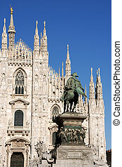 Gothic facade of Milan Cathedral in Piazza del Duomo. It is the fourth largest church in the world. The construction started in 1386 and took about five centuries. On the left the monument to king Vittorio Emanuele II.