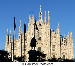 Milan duomo or cathedral against bright blue summer sky with silhouette of palm trees and king Victor Emanuel in front