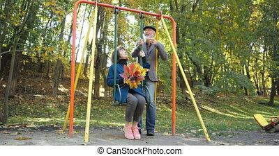 milieu, devant, mari, fond, épouse, couple, ensoleillé, parc, balancer, secousses, bouquet, gai, agréable, chaise, barbu, coup, automne, tenue, arbres, feuilles, sien, personnes agées, sourires
