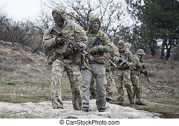 Military army soldiers team patrolling in forest