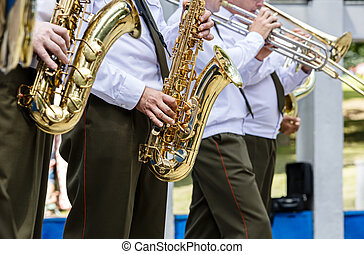 military brass band playing saxophones and trombones during music fest