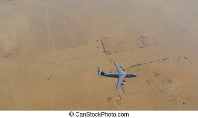 Military cargo aircraft flying over desert top view 4K - Top...