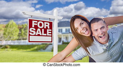 Military Couple In Front of Home with For Sale Sign