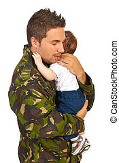 Military dad hugging his newborn baby son isolated on white...